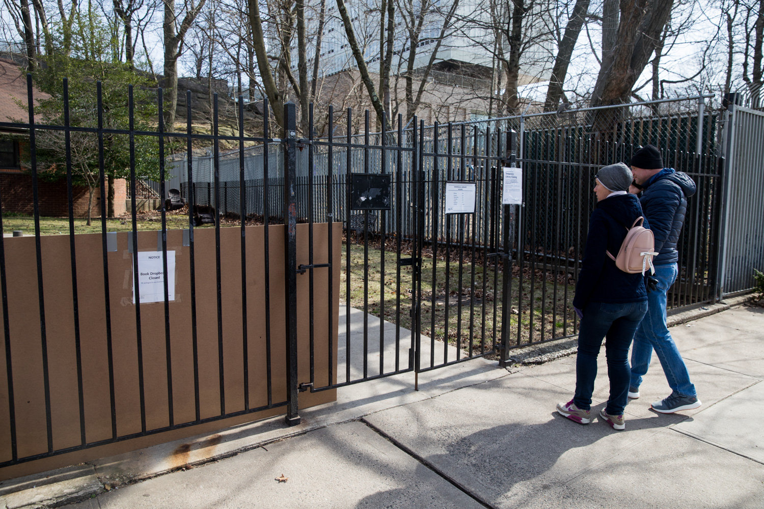 Passersby read the sign announcing the Riverdale Library's temporary closure in response to the coronavirus outbreak. The library is schedule to reopen March 31.