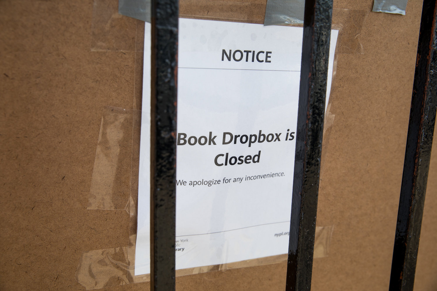A sign informs passersby that the Riverdale Library's book drop is temporarily closed.
