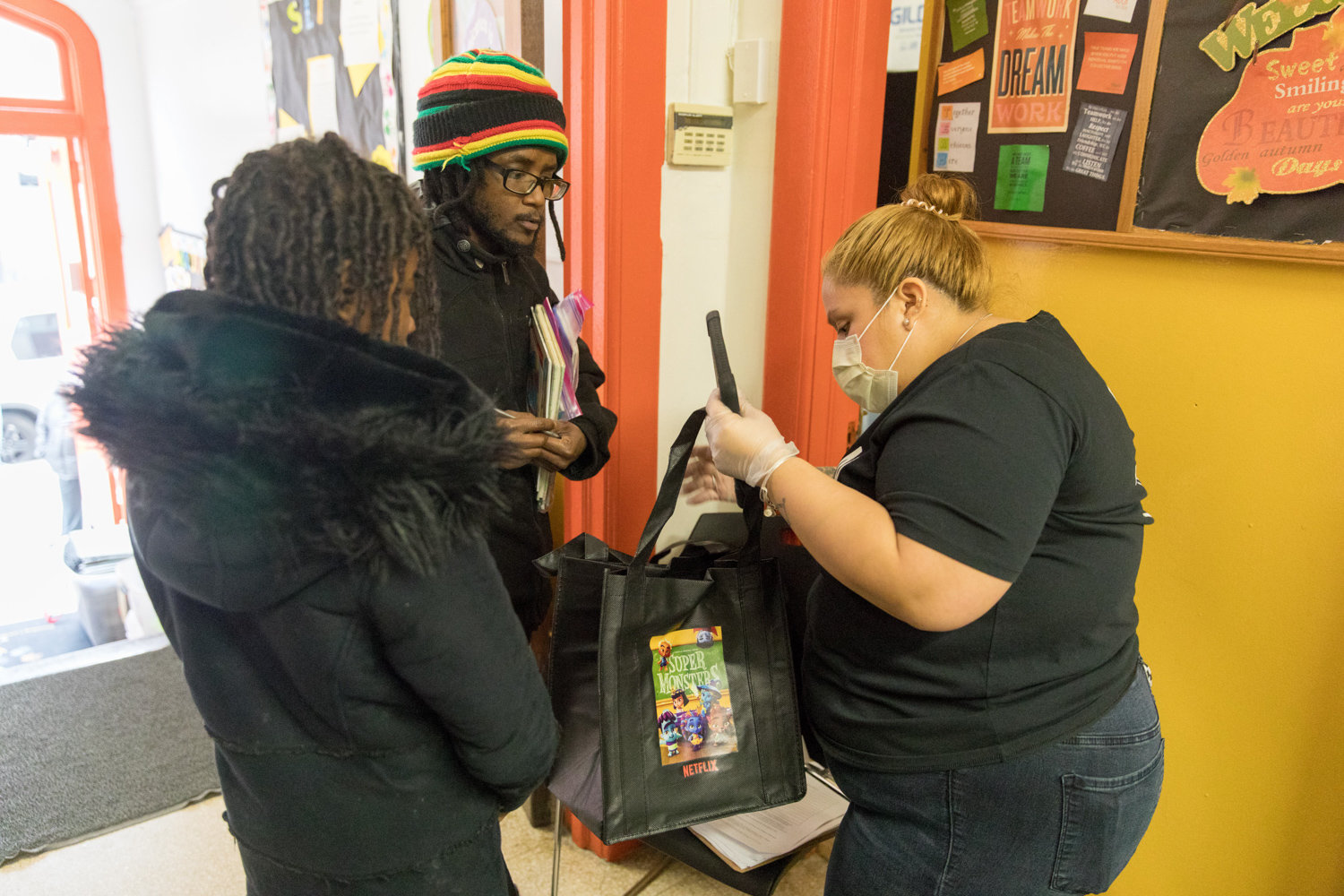 P.S. 207 aide Amy Jimenez hands bags of learning materials to Frederick Hay, the parent of three children enrolled at the Godwin Terrace school.