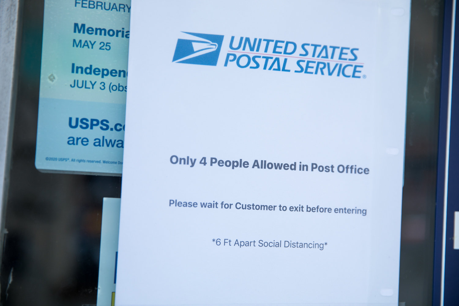 A sign informs people that due to social distancing guidelines caused by the coronavirus pandemic, only four people at a time are allowed inside the post office at 444 W. 238th St.