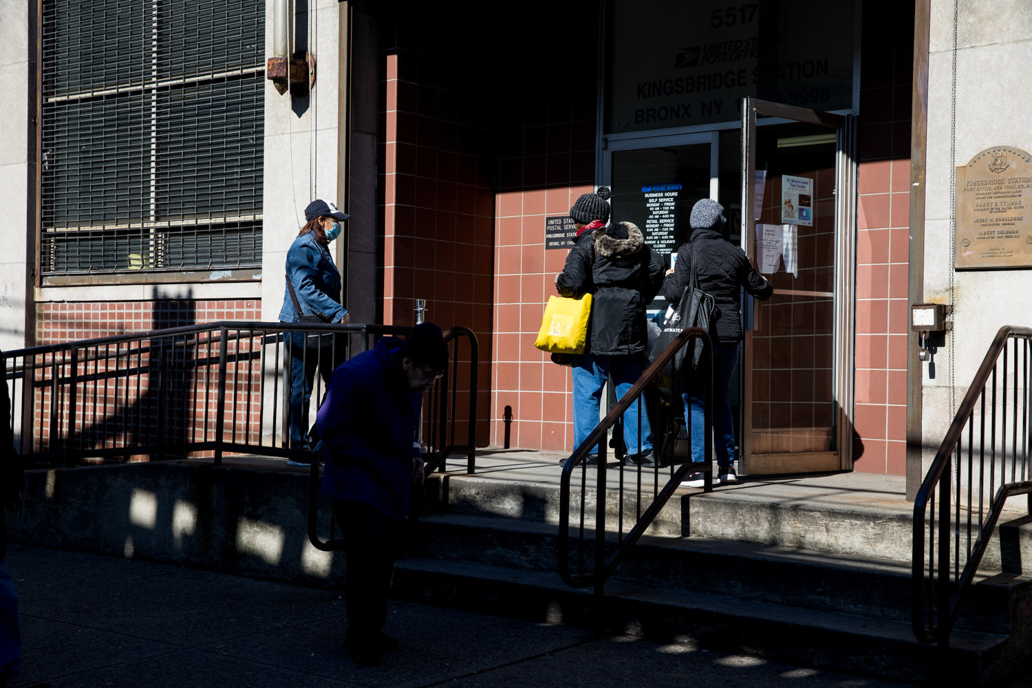 People enter and leave the post office on Broadway, which has recently suffered from understaffing — one of the reported causes of slowdown in mail delivery throughout the community.