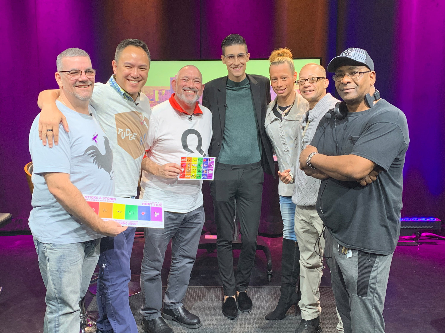 James Young, Geoff Peckman and Jeff Gurkin-Young of Queery, an LGBTQ education group, stands across from Sabastian Roy and Lailani Muniz of the New York Transgender Bodybuilding Federation with 'Out Loud' television host Anthony Parker right in the middle.