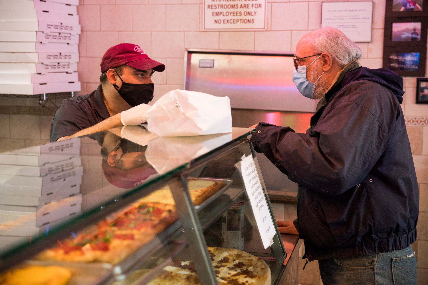Jody DePasquale, manager of Addeo's Riverdale Pizza, left, talks with a customer while filling his order. The North Riverdale pizza place has met the challenge posed by the coronavirus pandemic, managing to stay open. DePasquale and his workers have gone to greater lengths to help the community by running errands for customers.
