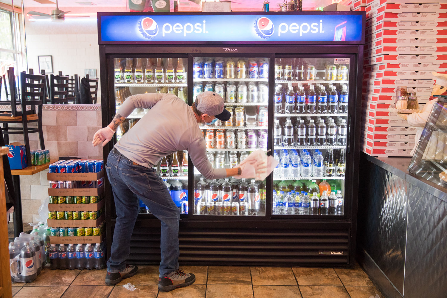 Shenol Mustafa wipes down a soda case inside Addeo's Riverdale Pizza, which has managed to stay open during the coronavirus pandemic.