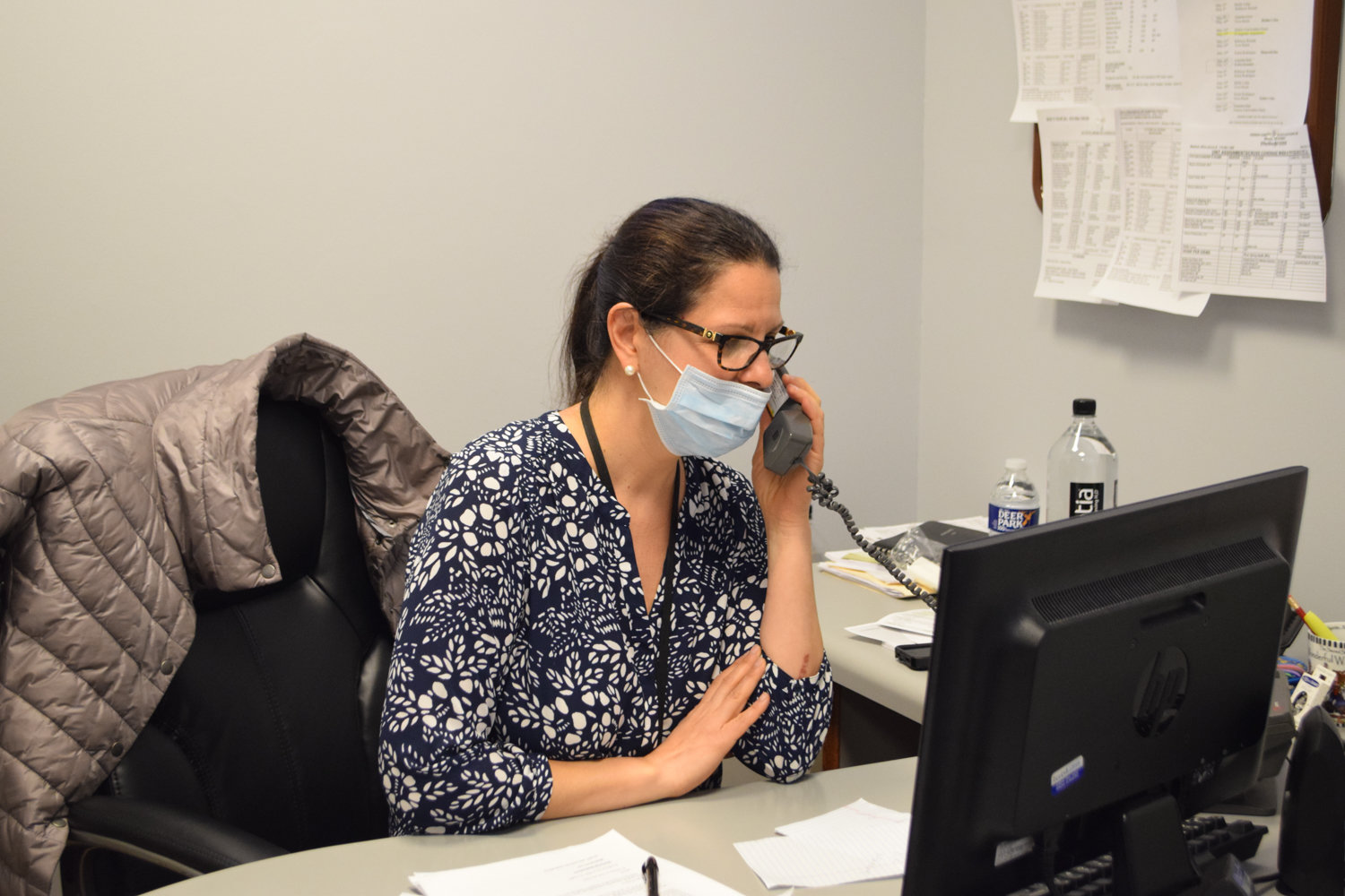 Evangeline Anastasiou, social services supervisor at the Hebrew Home at Riverdale, wears personal protective equipment at her desk. Since the advent of the coronavirus pandemic, the Hebrew Home has lost 25 residents from confirmed or suspected complications related to COVID-19.
