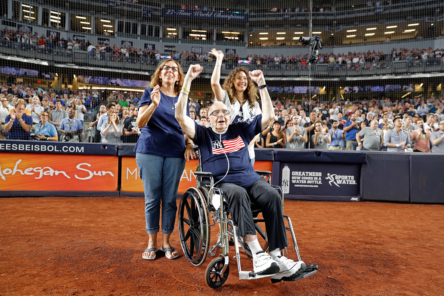 Alfred Schwartz cheers on the diamond at Yankee Stadium in 2018, joined by daughters Gayle and Heidi, right, who now grieve for him following his death on April 8 from complications related to COVID-19.