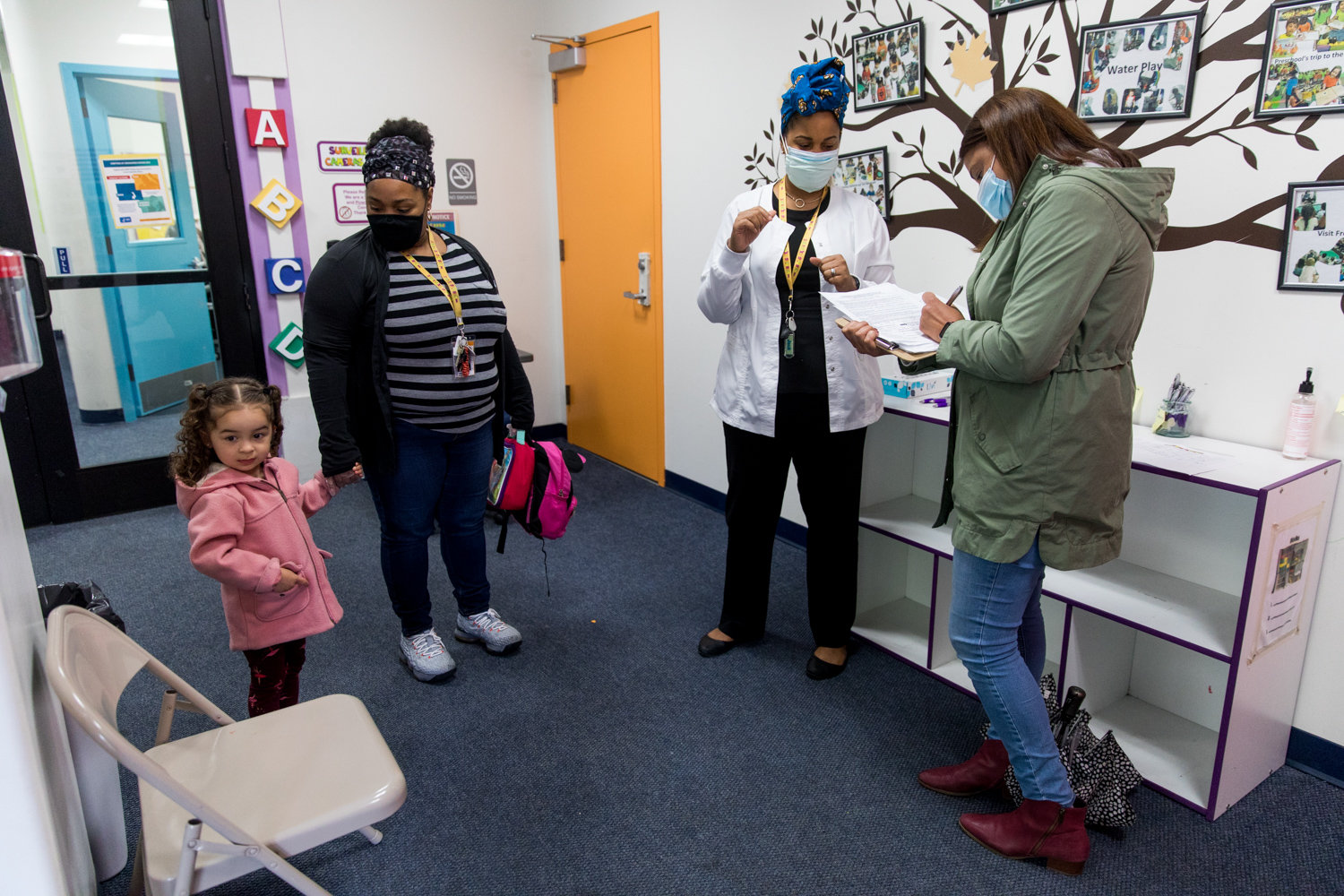 Roxana Vazquez, right, fills out a form while picking up her daughter Mia from The Learning Experience. It's at that Riverdale Avenue facility where Mia receives free care by day while Vazquez works as a clinical social worker in Westchester County.