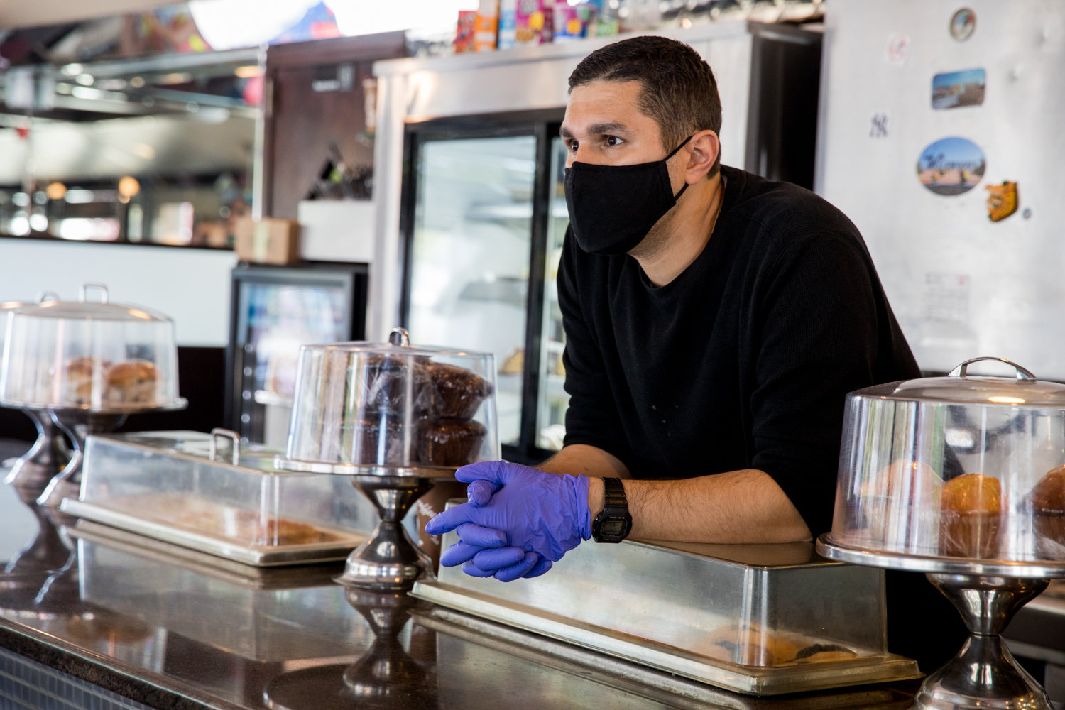 Nick Diakakis looks out from behind the counter at Tibbett Diner, which has been struggling in the face of the coronavirus pandemic. While it has reopened for takeout and delivery, business is not what it used to be.