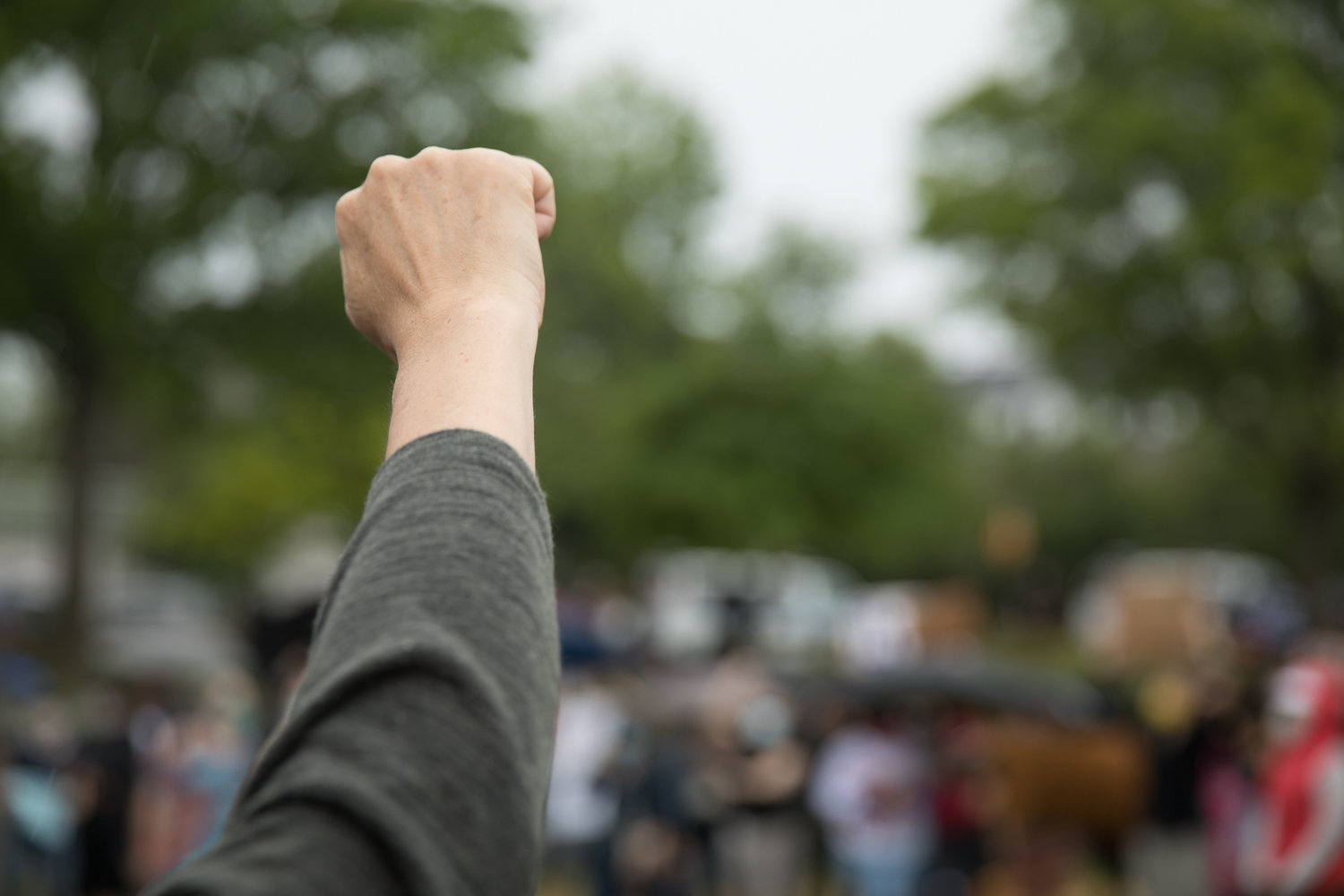 A community member raises her fist at a vigil in Seton Park honoring the lives of African Americans who died as a result of police brutality. The peaceful gathering was organized following rumors of a violent protest planned for the park that turned out to be untrue.