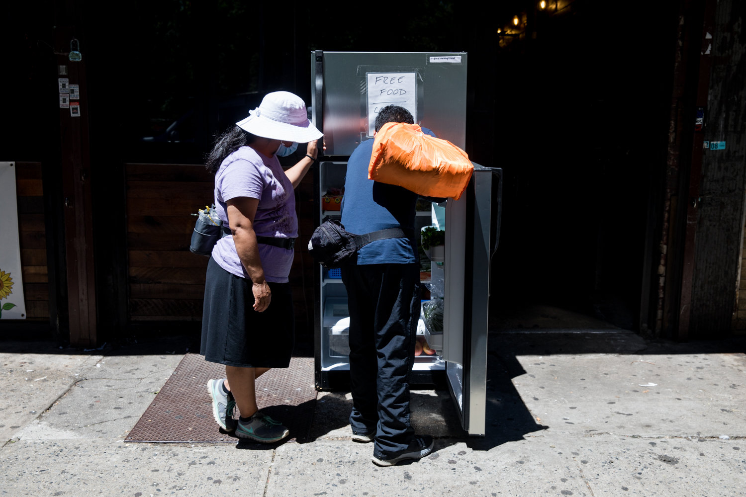 Passersby check a refrigerator outside The Last Stop on Broadway to see what food is available. The fridge there is part of a network across the city stocked by volunteers. Food is available for free to anyone who needs it.