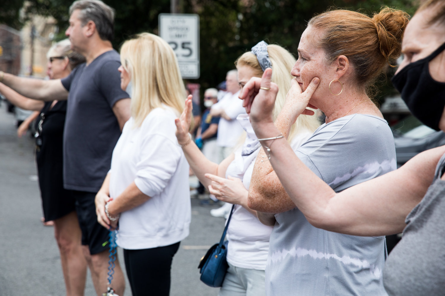 Mourners wave at a funeral procession for the late Michael Rooney on Mosholu Avenue. The procession down the avenue where Rooney lived was organized in light of the coronavirus pandemic to give those who knew him a chance to gather.