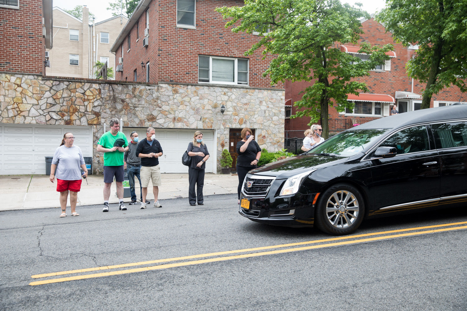 Mourners watch as a hearse carrying the late Michael Rooney makes its way down Mosholu Avenue where Rooney lived. A lifelong Riverdale resident, Rooney died June 3 at 65.