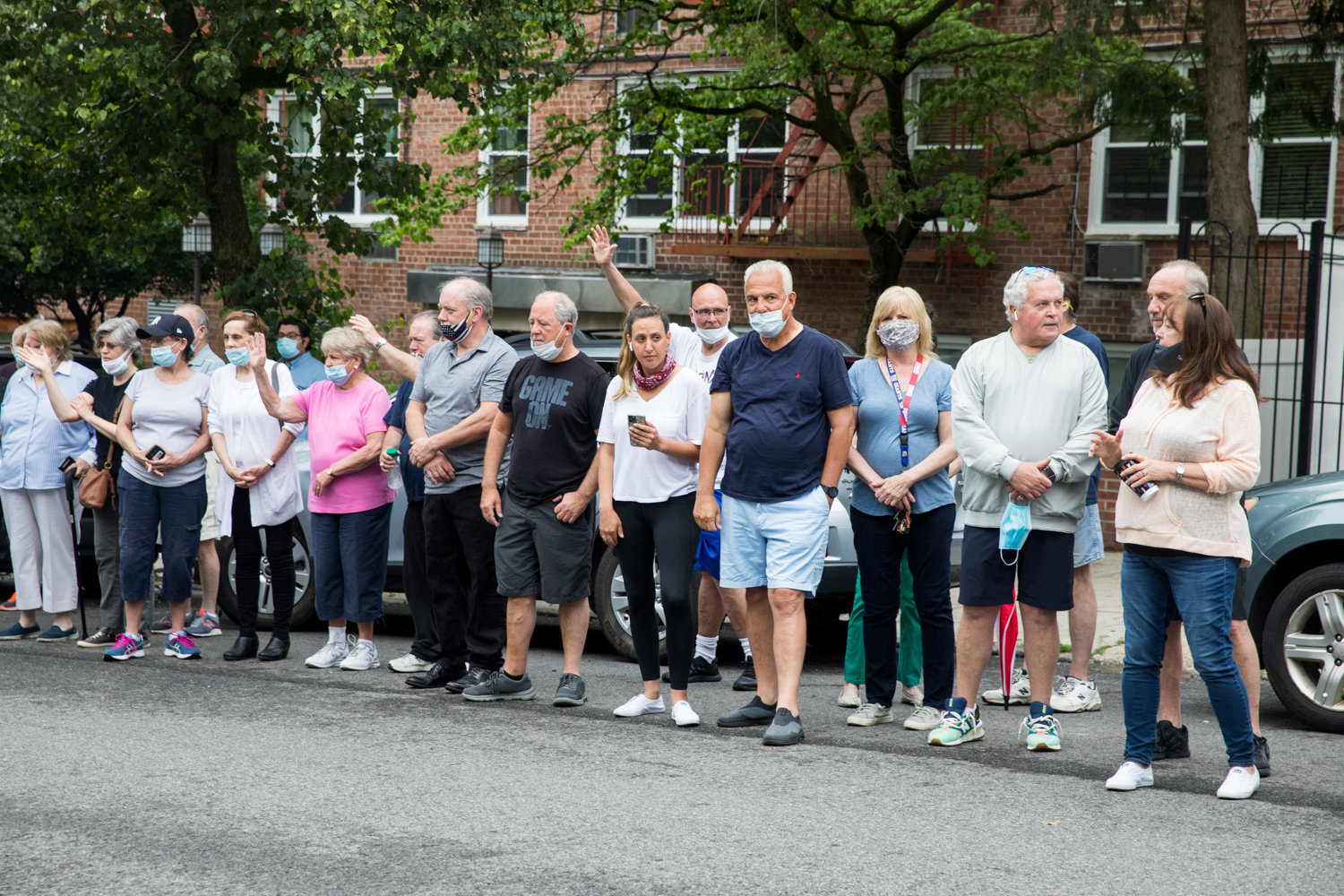Mourners stand on Mosholu Avenue during a funeral procession for the late Michael Rooney, a lifelong Riverdale resident.