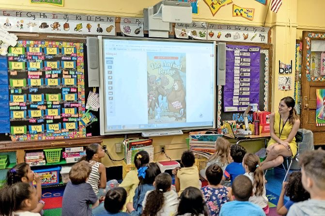 Alyssa Garraffo, a first grade teacher at P.S. 81, demonstrates showing a lesson on a smart board, an interactive display that allows teachers and students to work on in-class activities and lessons without wasting markers. P.S. 81 holds several parents association fundraisers throughout the year to help purchase materials for students.