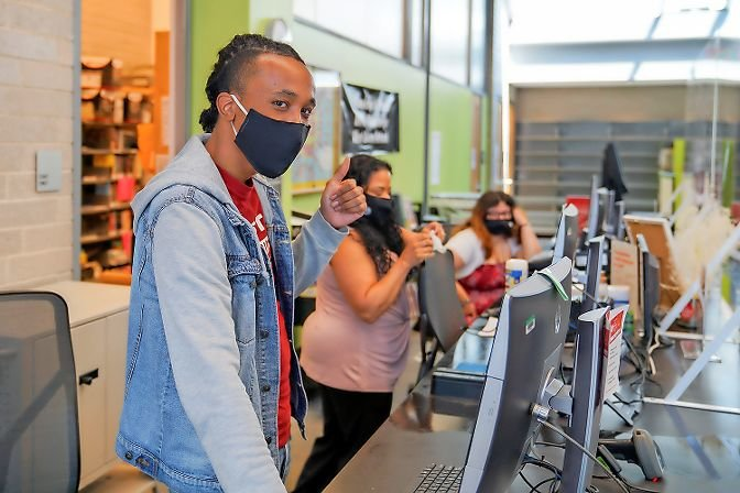 A librarian at Kingsbridge's West 231st Street branch gives a thumbs up on the location's first day back open to the public. Masks are required by both employees and patrons entering the building, and only grab-and-go services are being provided at this time.