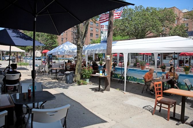 Sparse diners enjoy the shade of restaurant tents on Johnson Avenue on the first day of Open Streets Sundays, a program from the Kingsbridge Riverdale Van Cortlandt Development Corp., meant to provide socially distanced dining areas and stands for businesses and artists.