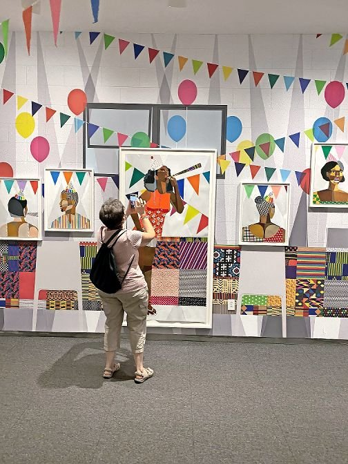 A visitor to the Hudson River Museum in Yonkers takes pictures of the recent Derrick Adams exhibit 'Buoyant,' which was reopened to the public at a limited capacity of 40 people. The museum has continued new exhibits and performances via its Amphitheater program, which accommodates 50 people, as the performance space is outside.