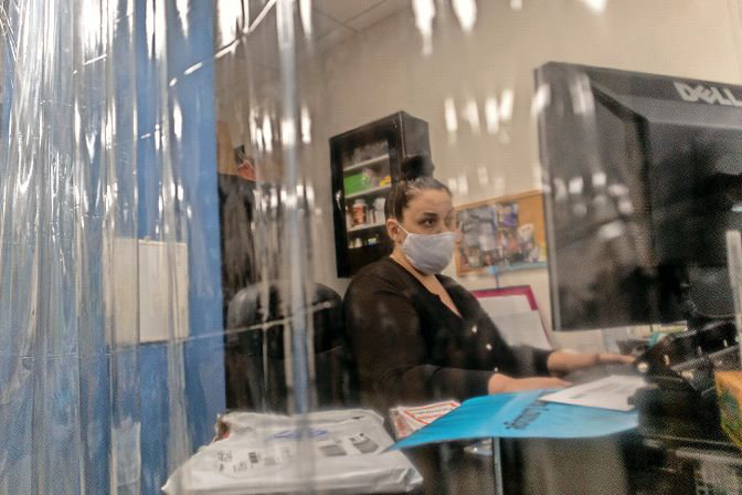An administrative staff member at Kinneret Day School works behind a plastic sheet, preparing for the arrival of students Sept. 8. The school originally closed in March, and has prepared for a physical campus reopening on Netherland Avenue since the summer began.