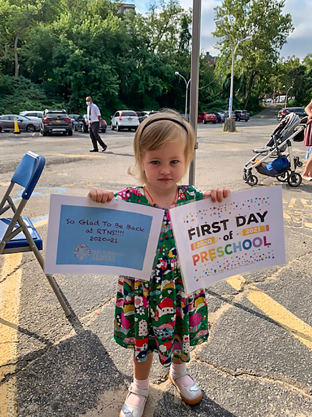 A preschooler shows off start-of-the-year print-outs at a Riverdale Temple Nursery School meet-and-greet. The school reopened earlier this month with the promise of in-person learning five days a week.