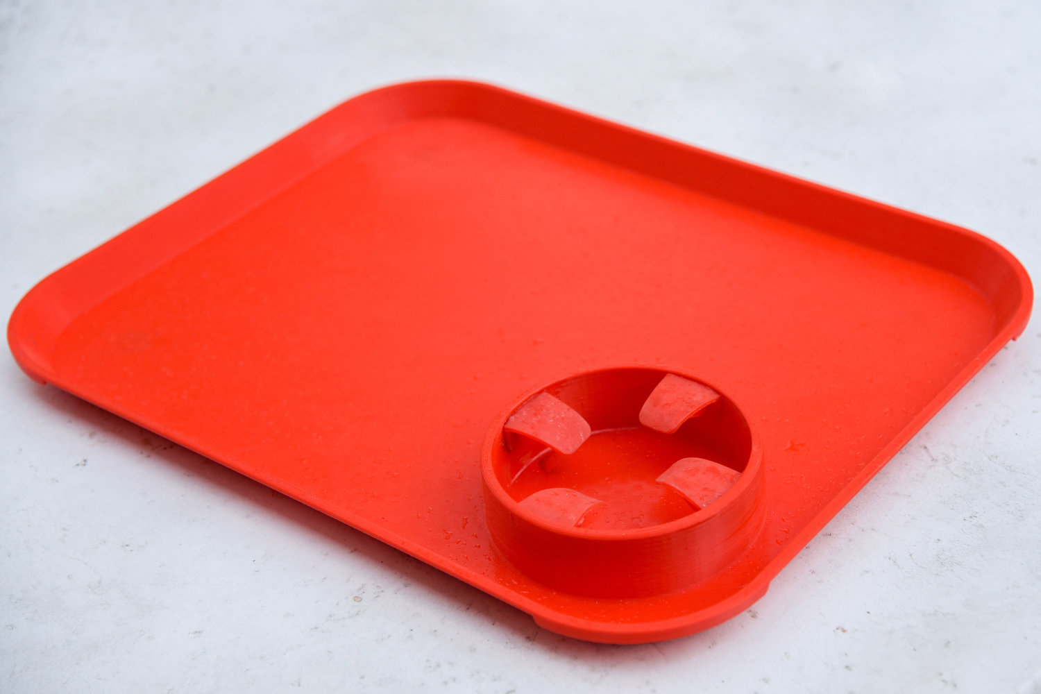 The independent feeding tray prototype features a molded cup with four flaps, intended to help stabilize the tray for those suffering from neurological conditions.