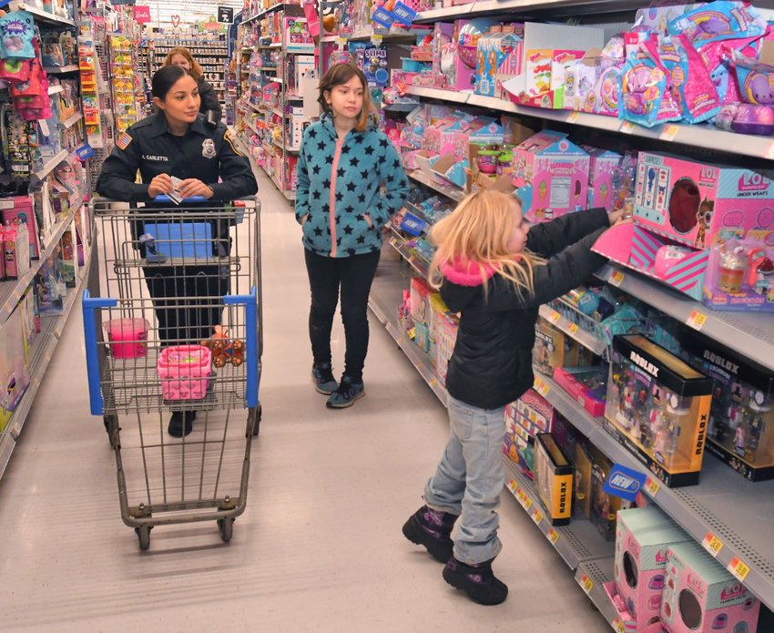 SHOP WITH A COP — Rome Police Department Officer Alexzandra Carletta pushes a shopping cart as Izabella Higby, 5, picks a toy from the aisle with big sister Hailey Higby, 14, looking on during this morning's annual Shop with a Cop charity event at Walmart. Rome police officers teamed up with more than 100 children from across the city to go on a shopping spree throughout the store. More pictures on page 3.