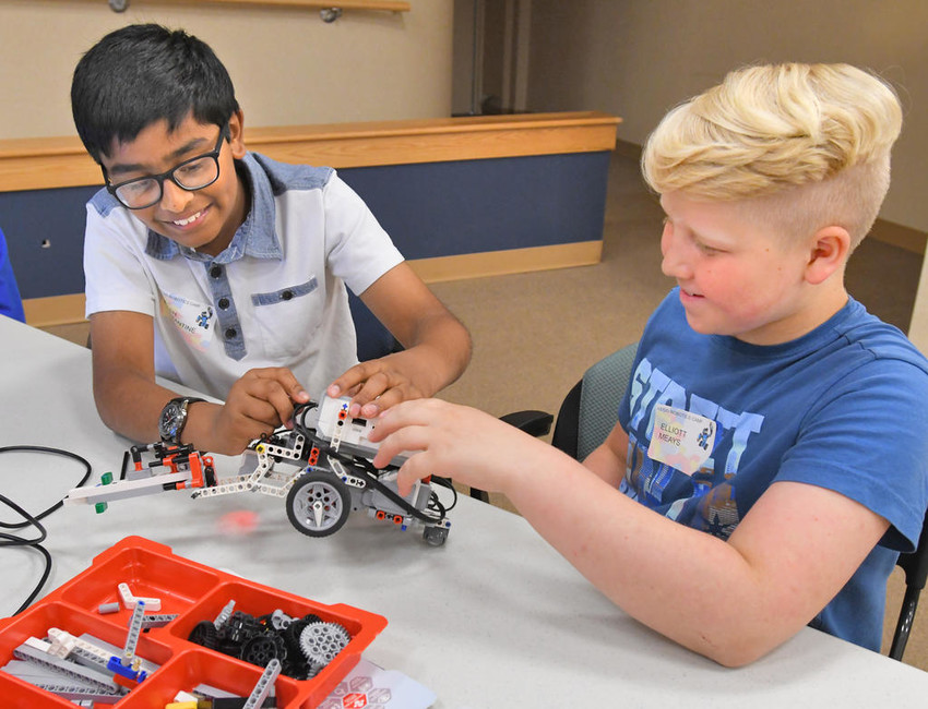 PUTTING IT TOGETHER — Students Nitesh Constantine from the New Hartford school district and Elliot Meays from the Holland Patent school district work on a robot Wednesday during a Lego Robotics camp at the Griffiss Institute. The camp, being conducted this week for area students, is part of a STEM (science, technology, engineering, math) Outreach Summer Program by the institute and the Rome Air Force Research Laboratory Information Directorate.  (Sentinel photo by John Clifford)