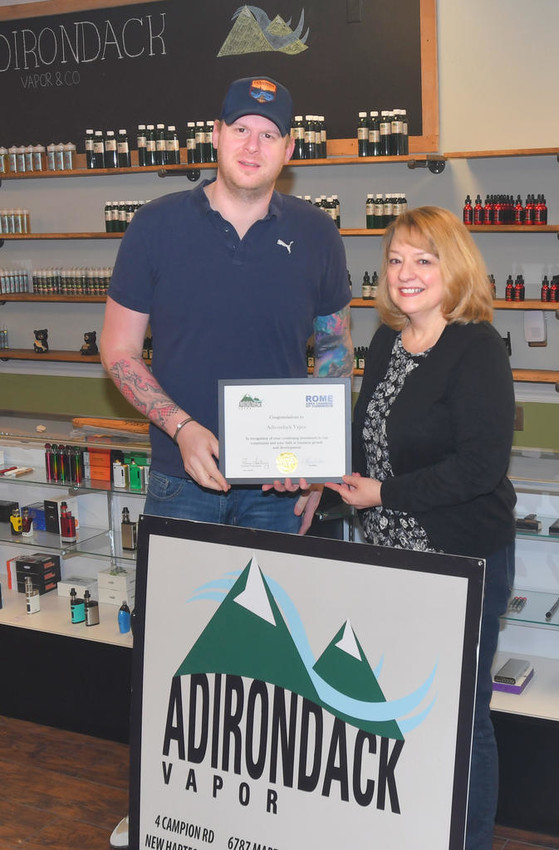 FIRST DOLLAR OF PROFIT — Sue McLoughlin, right, chairman of the Rome Area Chamber of Commerce Membership Committee, presents a First Dollar of Profit certificate to Adirondack Vapor owner Shane Carter. Adirondack Vapor is now located at 825 Black River Blvd., in the Black River Blvd. Shopping Plaza.  (Sentinel photo by John Clifford)