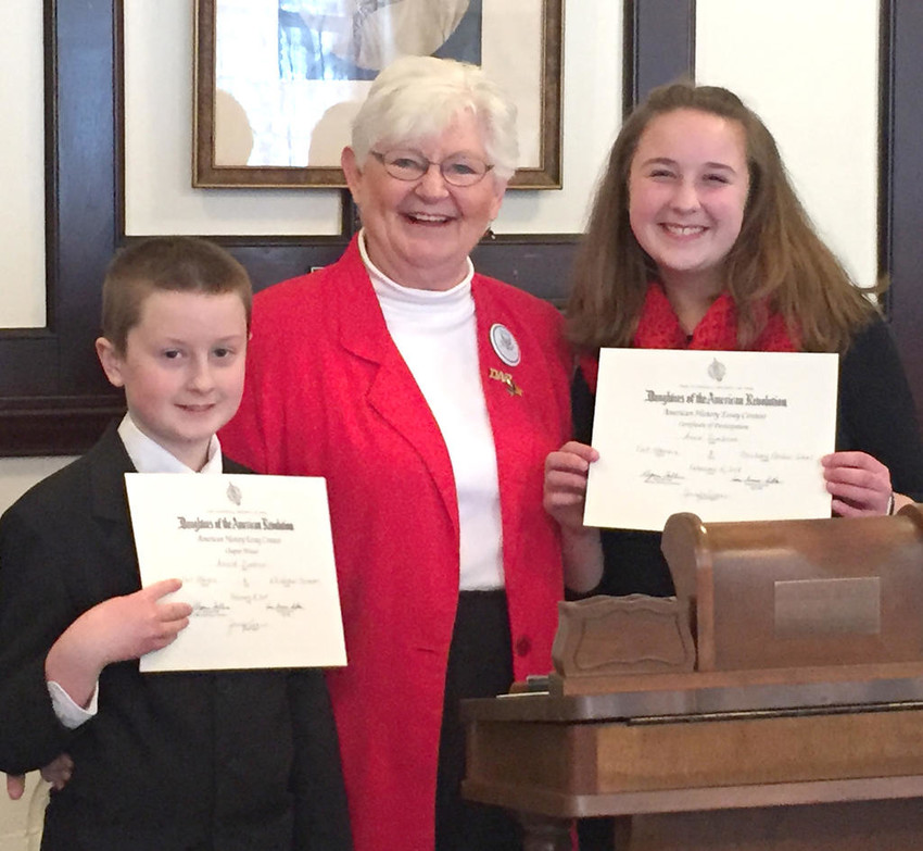 CONTEST WINNERS —The Fort Stanwix Chapter of the Daughters of the American Revolution presented American History Essay contest winners with awards during a recent ceremony at the First Baptist Church. From left: Sixth-grade winner Arnold Zumbrun; contest chair Judy Parker; and eighth-grade winner Anna Zumbrun. The students were presented with DAR history award medals, certificates and a cash prize. Both students are from Oriskany Central Schools.  (Photo submitted)