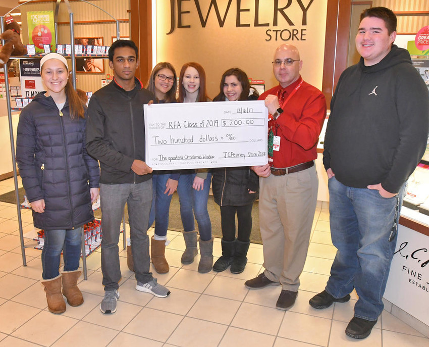 DONATION FOR WINNING ARTWORK — Rome Free Academy's Class of 2019 received a $200 JCPenney donation based on students' painting of a Christmas-themed window at the Rome store. Windows including one for each of RFA's four grades were painted last month, and members of the public were able to vote at the store for their favorite. Holding the left-side of the $200 check is RFA Class of 2019 member/window artist John George, while store manager Roger Houle holds the right-side.  From left: Class of 2018 member Caitlin Miller; George; RFA students Hailee Catalano, Karlee Tracy and Jordayn Purrington; Houle; and Class of 2018 member Aaron Cianfranco. Other participating Class of 2019 members, not shown in the photo, were Ann Marie Lawrence and Michaella Janes.  (Sentinel photo by John Clifford)