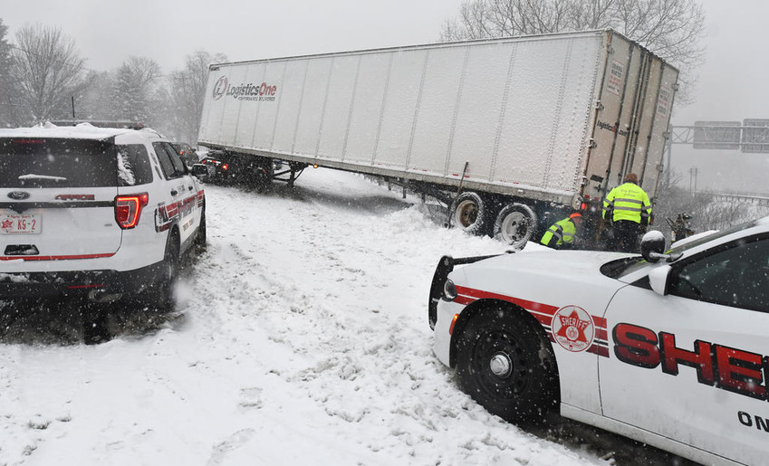 OFF THE ROAD — A crew from Greg Ellingers Collision work to free a trailer from a guard rail at the intersection of East Dominick Street and Route 49 this morning, one of several accidents reported on the roadways throughout the region.  Snowfall created hazardous road conditions for several morning commuters.  After a brief stoppage today, more snow is headed for the region this evening and tomorrow. See forecast, page 5.  (Sentinel photo by John Clifford)