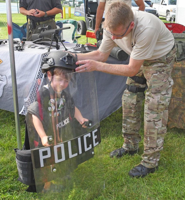 WIELD THE SHIELD —Bradley Cosser, age 3, grabs his riot shield and dons his gear with the help of Police Officer Scott Hoag at Law Enforcement Day Wednesday. Cosser was at Franklyn's Field with his mother, Kristin Cosser. Additional photos, pages 4 and 10.  (Sentinel photo by John Clifford)