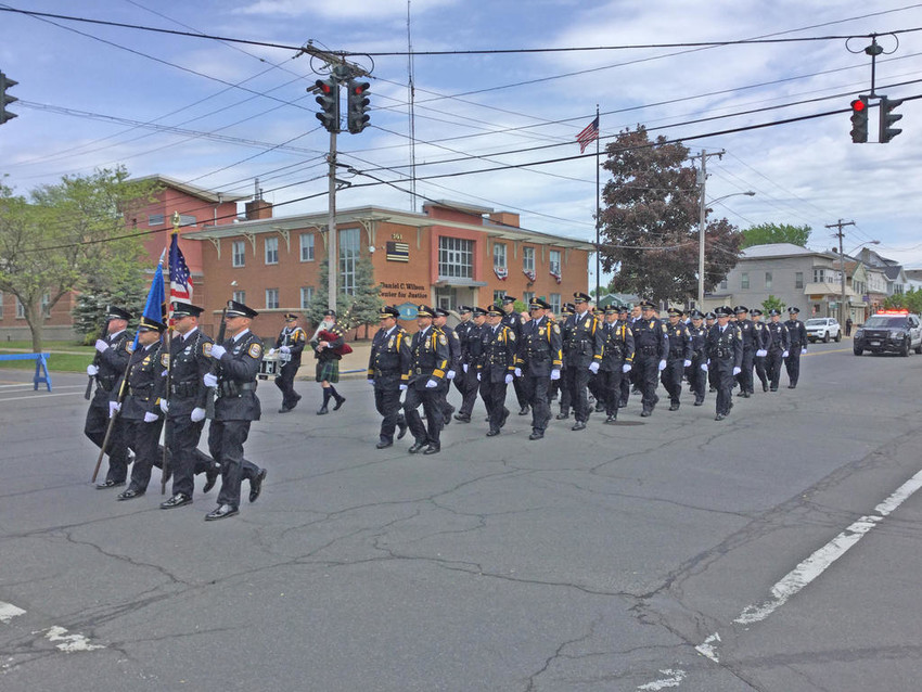 PROCESSION — Members of the Rome Police Department march down North James Street from the police station to St. Peter's Roman Catholic Church on Sunday.(Sentinel photos by Sean I. Mils)