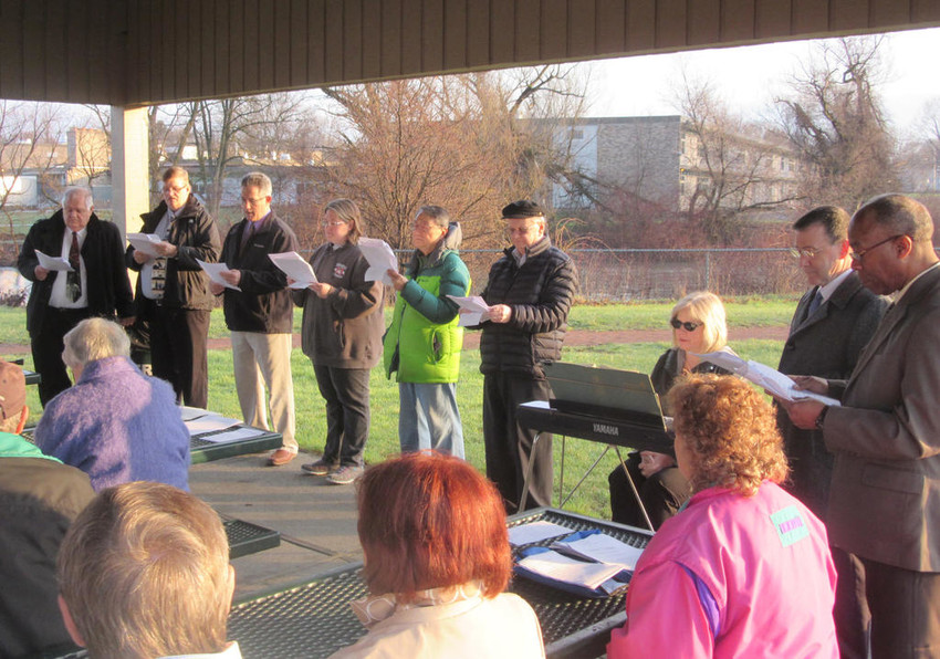 """PRESENT PROGRAM — Clergy presented a reading of """"The Tomb"""" Easter Sunday morning in the pavilion at Pinti Field across the Mohawk River from Staley Upper Elementary School.  From left,  the Rev. Dr. Andrew D. Peloubet,   the Rev. Tim Scott, the Rev. Rich Smith, Pastor  Wendy Morrison,  the Rev. Cedric A. Broughton,   pianist Carolyn Nelson,   the Rev. Sam Pendergrast,  and the Rev. Willard Scott.  (Sentinel photo by Norm Landis)"""