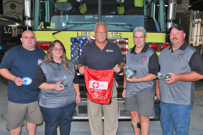 PET OXYGEN MASKS DONATED — Three pet oxygen masks in small, medium and large sizes have been donated to the Lee Center Volunteer Fire Department. From left: James Fisher, fire department second lieutenant; Laura Kinney, department emergency medical services director; Kurt Grage, owner/president of Invisible Fence of the Finger Lakes, Midstate and Syracuse, which donated the masks; fire department member Carol Kieffer, who inquired about the masks after several dogs and cats perished in a July fire on Stokes-Westernville Road; and Lee Center Fire Chief James Rouillier. Grage said the overall Invisible Fence Brand company, which includes electronic pet containment systems, has donated the oxygen masks to fire departments, emergency medical, animal rescue and related organizations in the U.S. and Canada for about 12 years. The company has about 290 dealers in those countries.  (Sentinel photo by John Clifford)