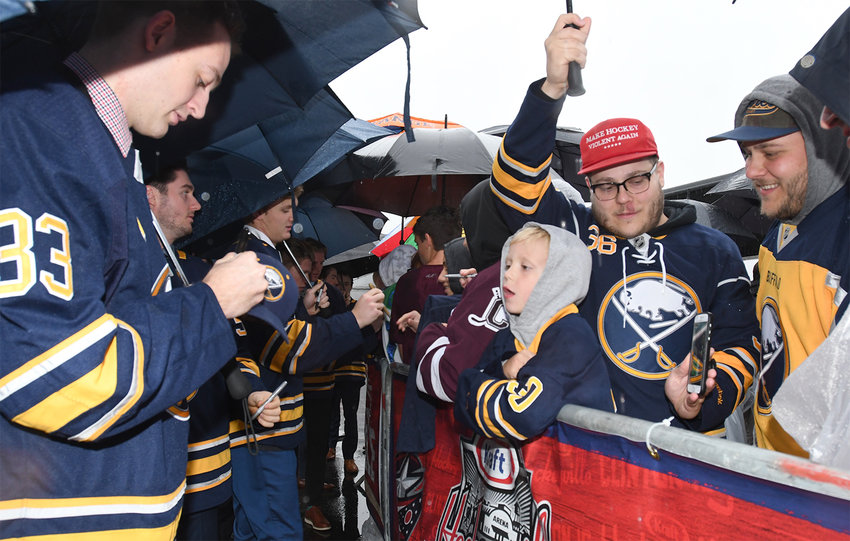 GIVING A SOUVENIR — Buffalo Sabres defenseman William Borgen, left, signs an autograph for three-year-old Lincoln Klosek as his uncle James Klosek holds an umbrella and his dad Tom Klosek, right, looks on during NHL players arrival on the red carpet on Sept. 25 at Clinton Arena. The Kloseks are from Clinton.
