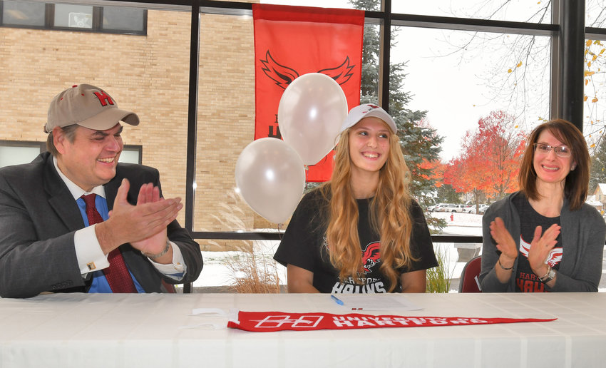 GO HAWKS — Clinton High School senior Olivia Wightman and her parents Rob Wightman and Cathy Surace clap for their daughter after she signs her national letter of intent to go to Hartford University for lacrosse.