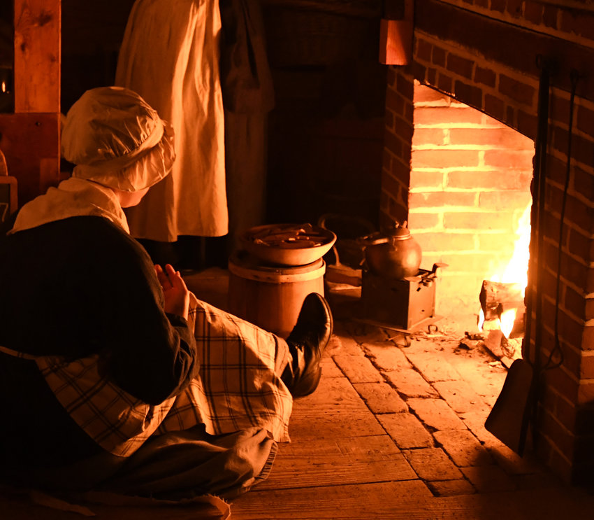 HOME IS WHERE THE HEARTH IS —A volunteer colonial re-enactor keeps warm by the fire in the German Room at Fort Stanwix National Monument in this 2017 file photo. Dozens of historic re-enactors will help share what the holidays were like in the Mohawk Valley during the 18th century as part of Fort Stanwix's annual holiday celebration. A schedule of events for 2018 will be posted soon at Fort Stanwix's website: www.nps.gov/fost.