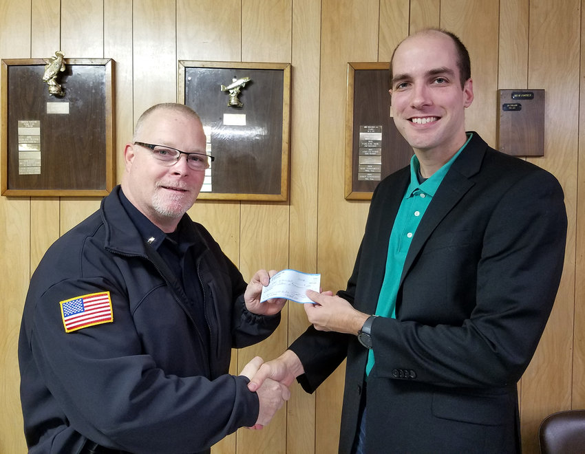 SHOP WITH COP DONATION — From left, Rome Police Lt. Tom Smith is presented with a $1,000 donation for the police department's Shop with a Cop program from Greenway-Verona Mills Fish and Game Club President Mark Gymburch. The club raised money through 50/50 raffles and member donations at its monthly meetings throughout the year in support of the police department program, in which underprivileged children receive gift cards and are taken Christmas shopping by police officers.