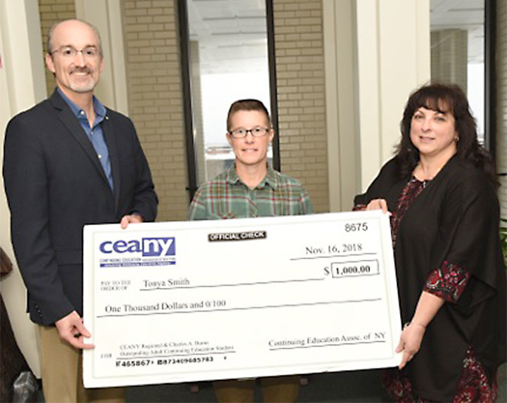 SCHOLARSHIP CHECK — MVCC President Randall VanWagoner and Coordinator of Adult Learner Services Janet Visalli present Tonya Smith with a $1,000 scholarship check for her CEANY award.