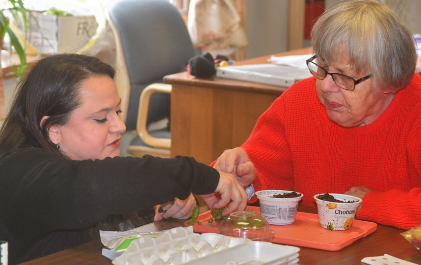 UPCYCLING — Christina Carambia owner of Underground Greens and the designer of the Makers Club at SUNY Poly where she is a student helps Georgeanna Howanietz with a bedazzled plant pot that she will grow basil in at the Ava Dorfman Senior center Thursday afternoon.