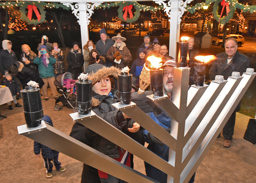 FESTIVAL OF LIGHTS — Leor Grysmintz, 4, gets help from Steven Marcus to light one of the candles of the menorah at the Village Green gazebo in Clinton on Dec. 6.