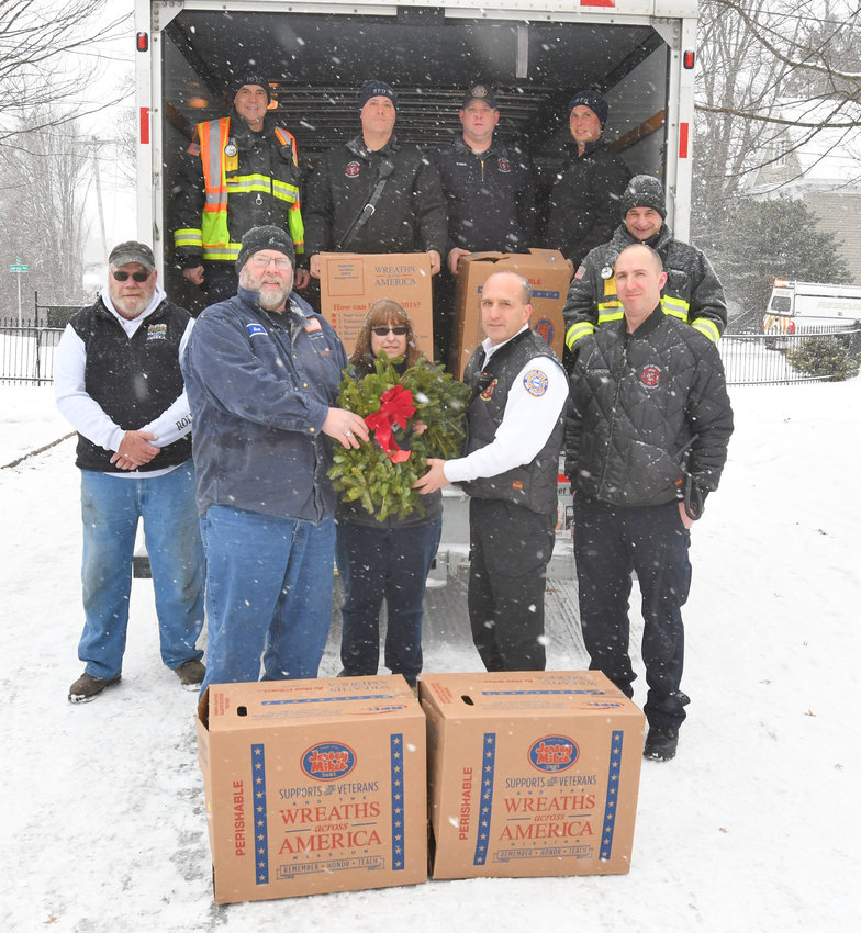 UNLOADING — Boxes of wreaths to be used in ceremonies remembering deceased veterans from across the area arrive and are unloaded this morning at Rome Cemetery on Jervis Avenue.  From left, Mike Homer; Kent Tryon, owner of Tryon Transfer; Malinda Abraham, Rome Cemetery office manager; Deputy Fire Chief David Gratch; and fire Lt. Keith Gorczyca. In the truck are Rome firemen Mike Bauer, Lenny Cianfrocco, Phil Diehl, Pat Mumford and Joe Ferrare. The firefighters helped to unloaded the truck in about 15 minutes with half going into the Rome Cemetery and the others going into a moving truck, donated by Uhaul Moving and Storage of Rome, which will distribute wreaths to other cemeteries in the area. An article outlining on Saturday's ceremonies will be published in Friday's edition.