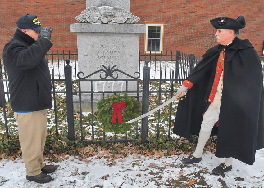 REMEMBERING THE DECEASED — Steve Mercurio, left, representing the Greater Utica Rome Chapter Officers Association of America, and Bob Allers, representing a Continental Artillaryman, salute as a wreath is placed at the Tomb of the Unknown Revolutionary War Soldier at the corner of North James and Liberty Streets this morning.