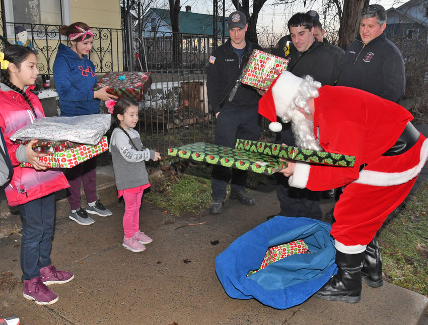 SANTA'S IN TOWN — Santa Claus came early to Fourth Street Friday night, delivering gifts to Paige Lugo, age 11, and Alana Jimenez, age 4, with their mother, Francesca Jimenez, looking on. Santa was aided on his visit by Rome firefighters Paul Matwijec, Canio Sabia, Marco DiCastro, Eddie Marsh and Lt. Jason Livingston. Additional photos, page 3.