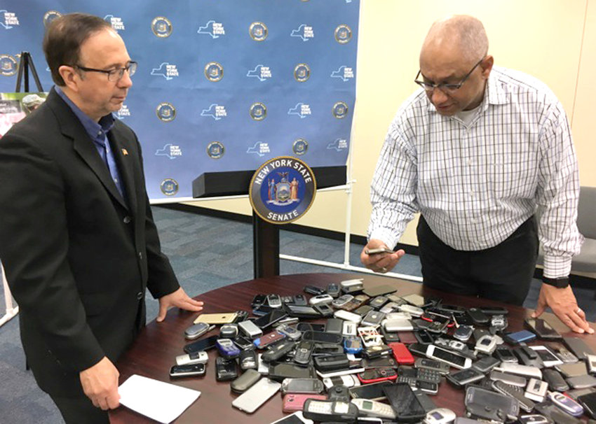 PHONE HOME —  State Sen. Joseph Griffo, R-Rome, and Greeley Ford of AT&T check out some of the mobile phones donated as part of a monthlong cell phone collection drive in Griffo's 47th Senate district.