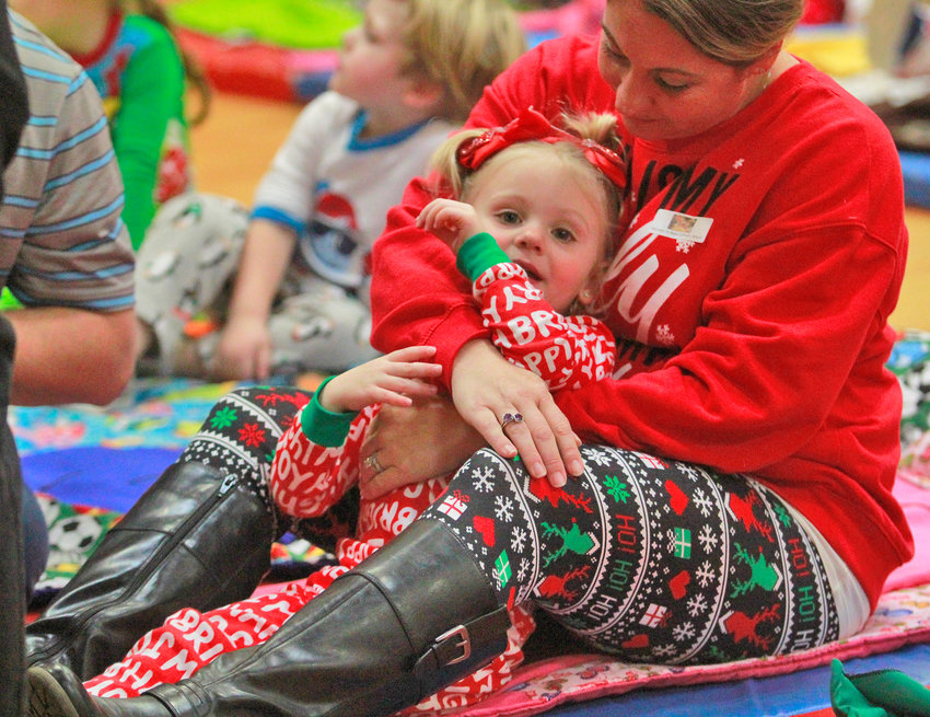 CUDDLE TIME — Madelin Colosimo, 3, snuggles with her mother Michelle Colosimo before the start of a pajama party and movie-watching event Friday at Rome Catholic School. It was part of a Christmas celebration at the school.