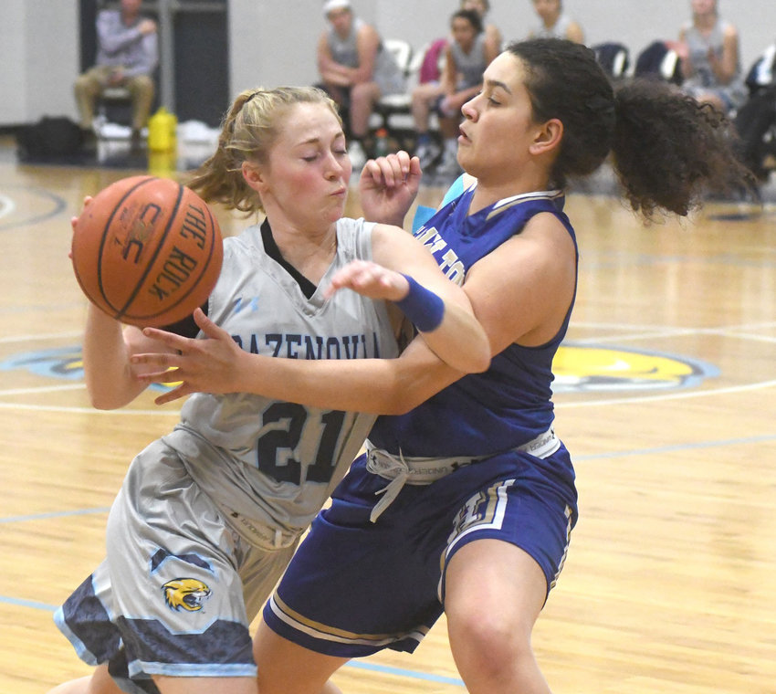 COMIN' ON THROUGH — Amy Holland lowers shoulder and muscles her way to the basket against the Hamilton Continentals. Holland scored a team high 16 points and had five rebounds and three each assists and steals in the contest.