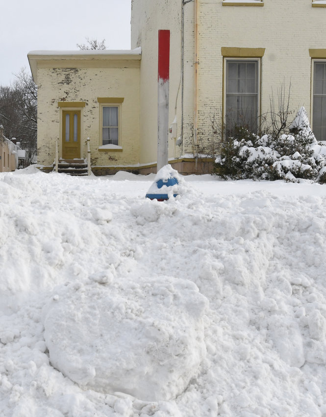 DIG IT OUT — A fire hydrant remains buried in deep snow in front of the old Arsenal House on West Dominick Street this morning. Fire officials ask that you clear out at least 3-feet of snow from around your nearby fire hydrants to help in case of a nearby house fire.