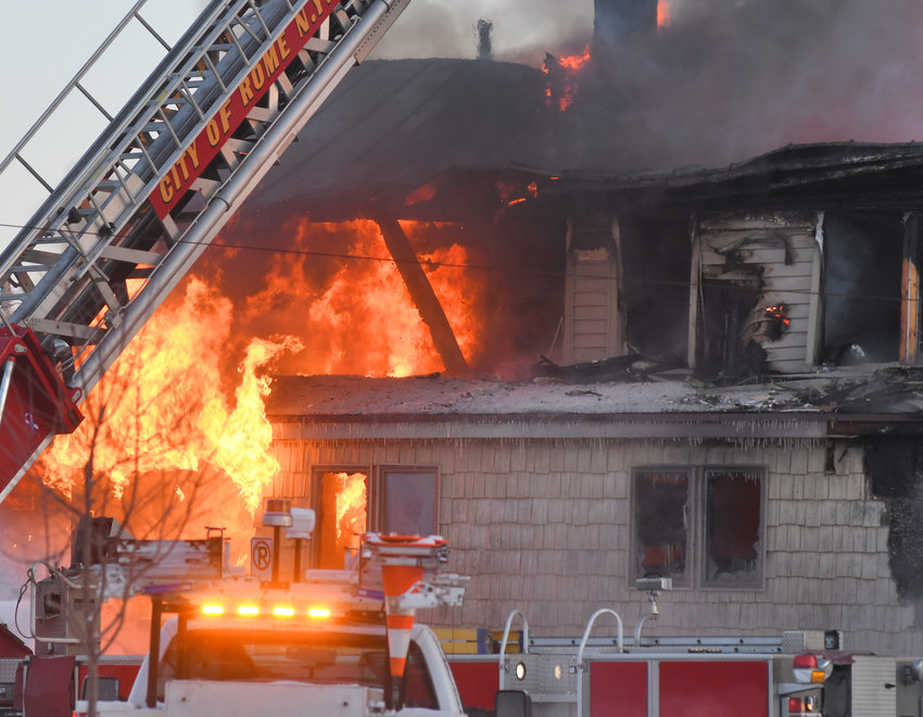RAGING FIRE —Bright orange flames break through the backside of Peterson's Exotic Pets during this morning's early fire. The city's aerial truck was raised high above the block to shoot down into the burning buildings.