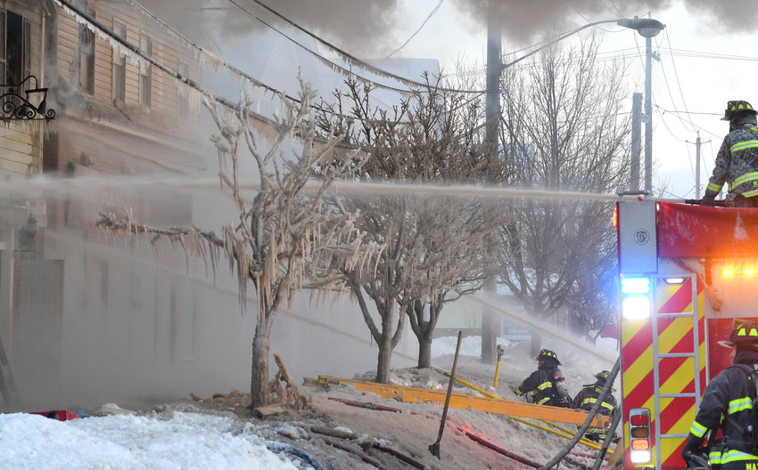 STILL WORKING —Firefighters battle the blaze at 305 N. James St. this morning, dousing flames as icycles hang from trees in front of the building and smoke billows into the morning sky.